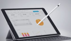 ipad and stylus with business charts and graphs
